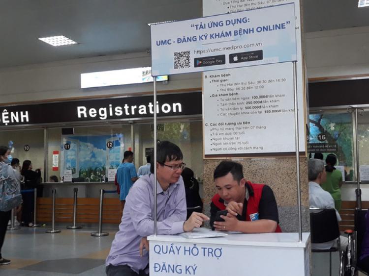 Người dân cài ứng dụng đăng ký khám bệnh online tại Bệnh viện ĐH Y Dược TP.HCM - Ảnh: Hoàng Lộc
